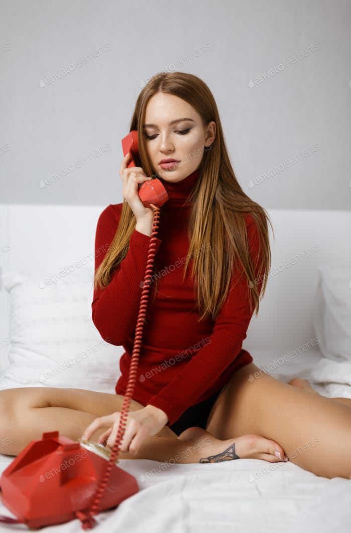 Young thoughtful lady with straight hair sitting in bed and dialing number on red classic telephone