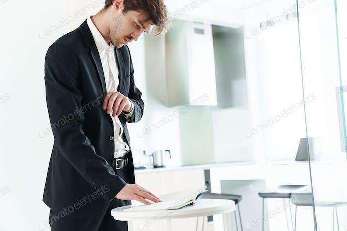 Foto von ernsthaften unrasierten Geschäftsmann Prüfung Planer