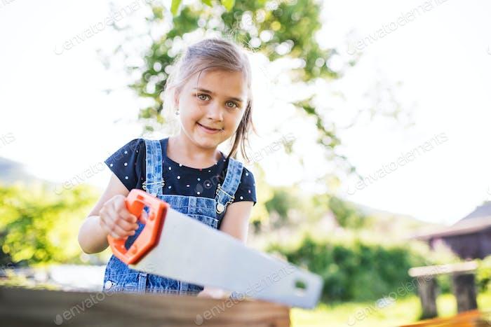 Ein kleines Mädchen mit einer Säge draußen, die ein hölzernes Vogelhaus macht.
