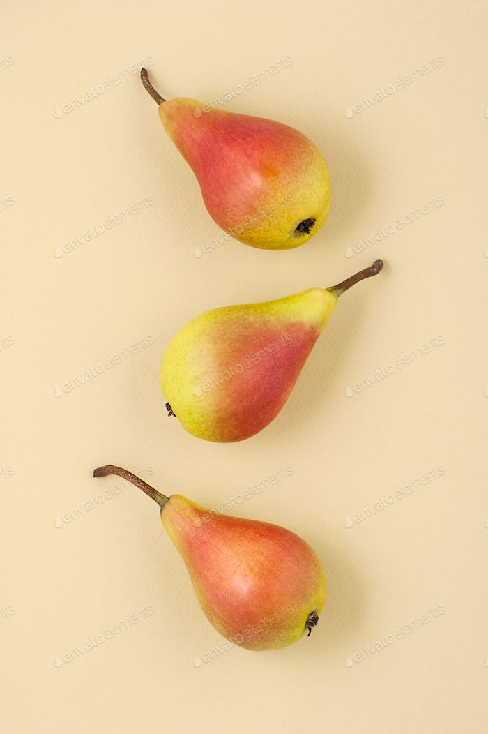Three ripe juicy pears on a light yellow pastel background.