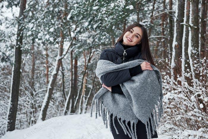 Porträt einer bezaubernden Frau in der schwarzen Jacke und dem grauen Schal im Winterwald