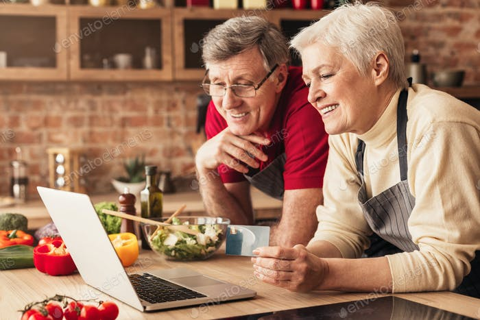 Happy seniors ordering dinner online on laptop and credit card at kitchen