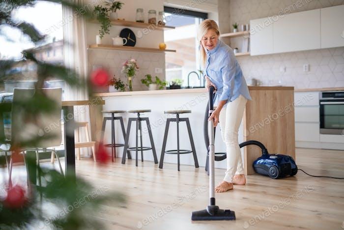 Senior Frau mit Staubsauger drinnen zu Hause zu Weihnachten Zeit, Hoover