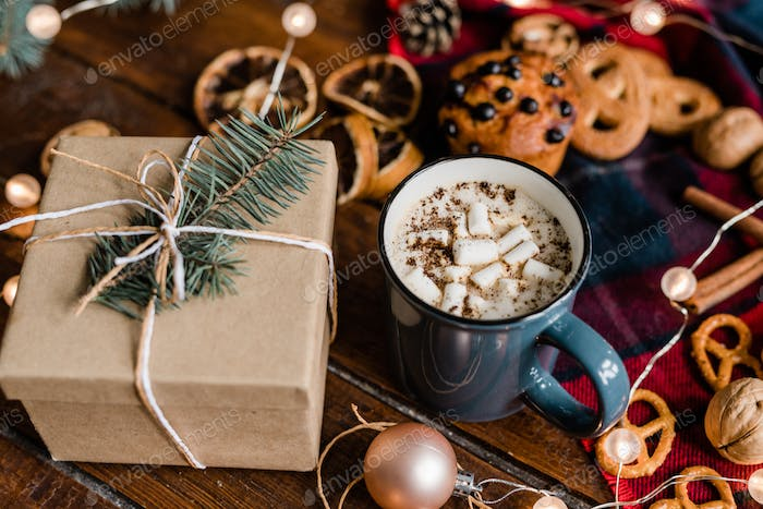 Mug with hot coffee, giftbox with conifer on top, cookies and garland