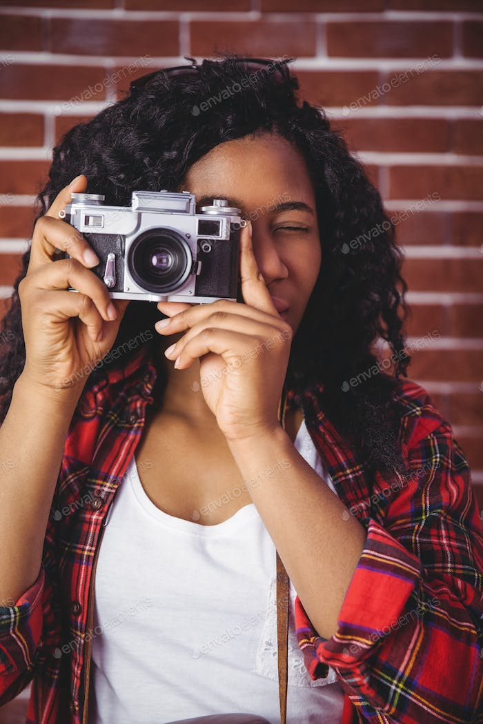 Hipster using a retro style camera on red brick background