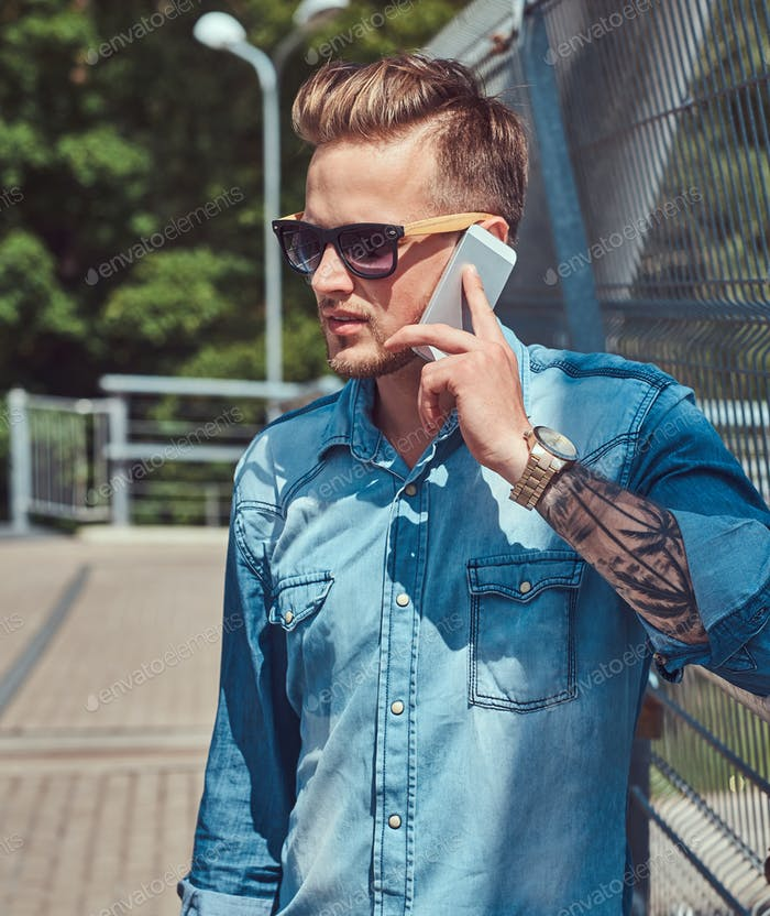 Handsome hipster in sunglasses resting after riding on a bicycle, using a smartphone.