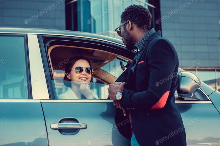 Casual couple posing near a car.