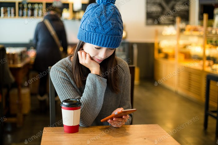 Woman use of mobile phone in coffee shop