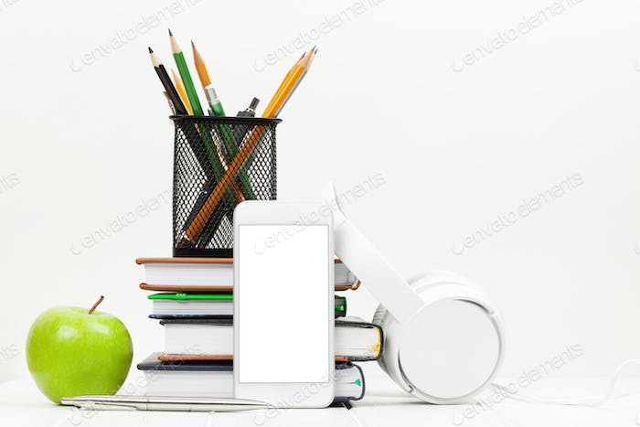 Workplace with smartphone, supplies and apple