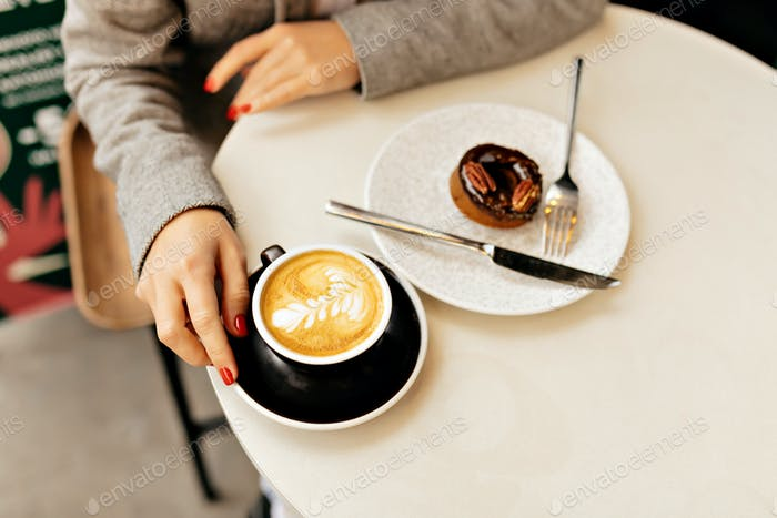 Above frame of woman's hand with cappuccino and donut on white table