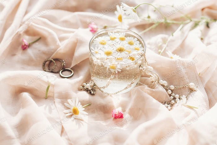 Daisy flowers in water in glass cup on background of soft beige fabric with wildflowers and jewelry