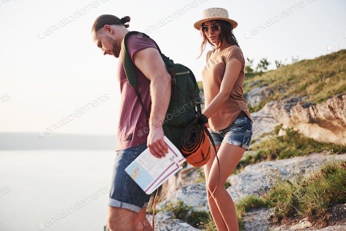 Zwei Tourist mit Rucksäcken klettern auf die Spitze des Berges und genießen Sonnenaufgang