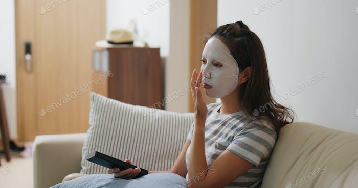 Frau gelten Gesichtsmaske und fernsehen zu Hause