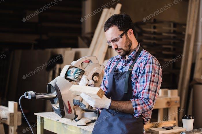 Schöner Zimmermann in Schutzbrille stehend in der Nähe seines hölzernen Objekts in der Werkstatt