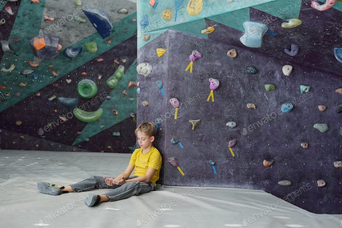 Youthful boy looking at his hands while sitting on mat by climbing equipment