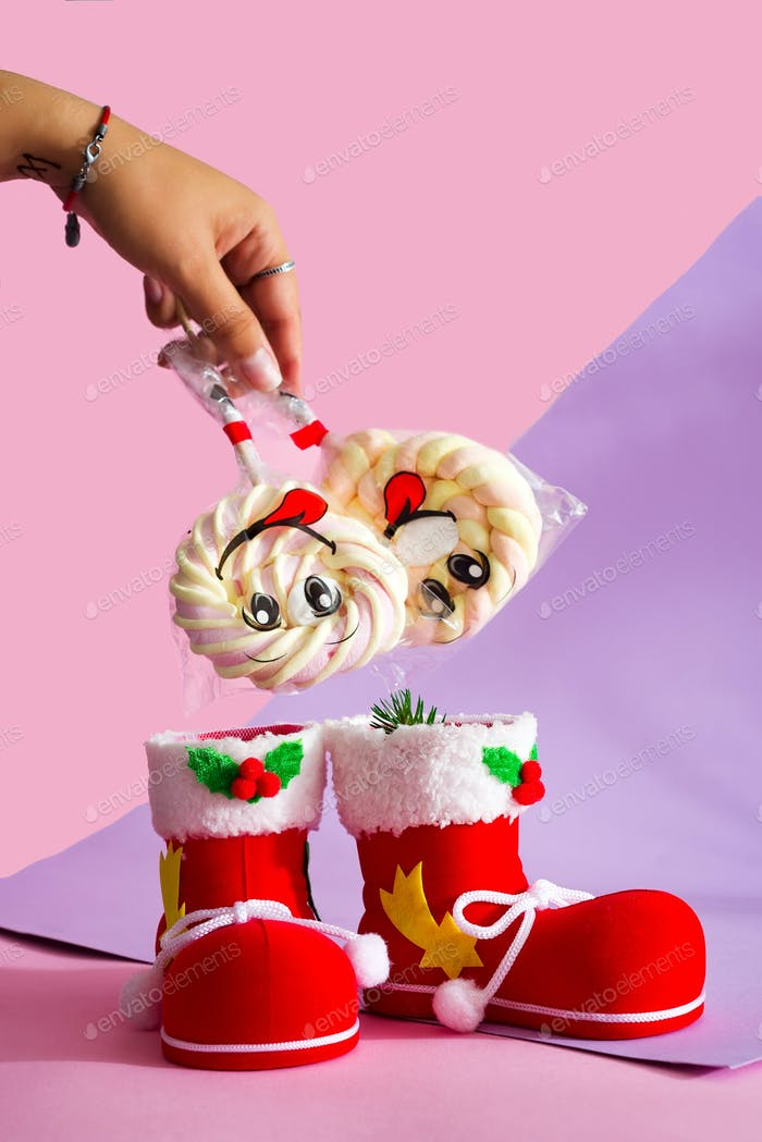 Santa's boot with candy marshmallow on a stick with a smile on the duotone background