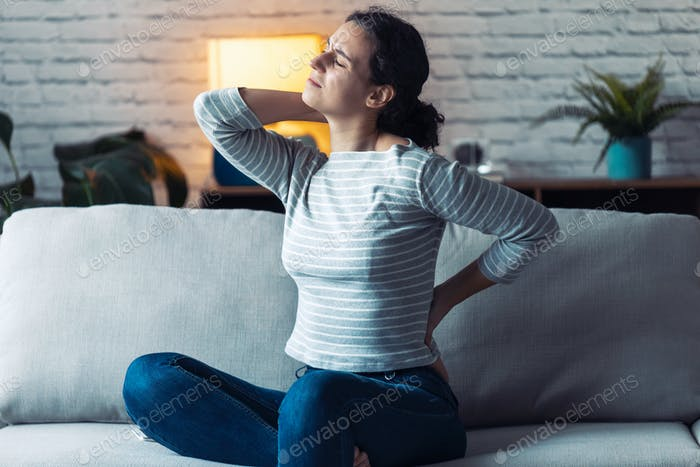 Young woman with back and neck pain sitting on the sofa in the living room at home.