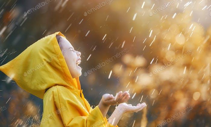 Kind unter Herbst regen