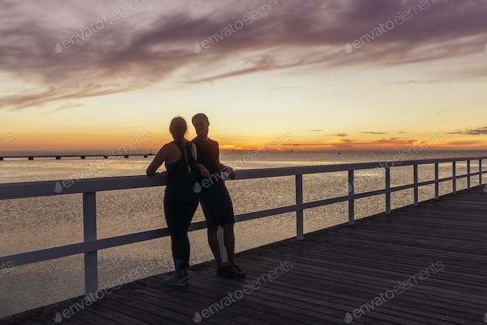 Young couple standing on pier at sunset