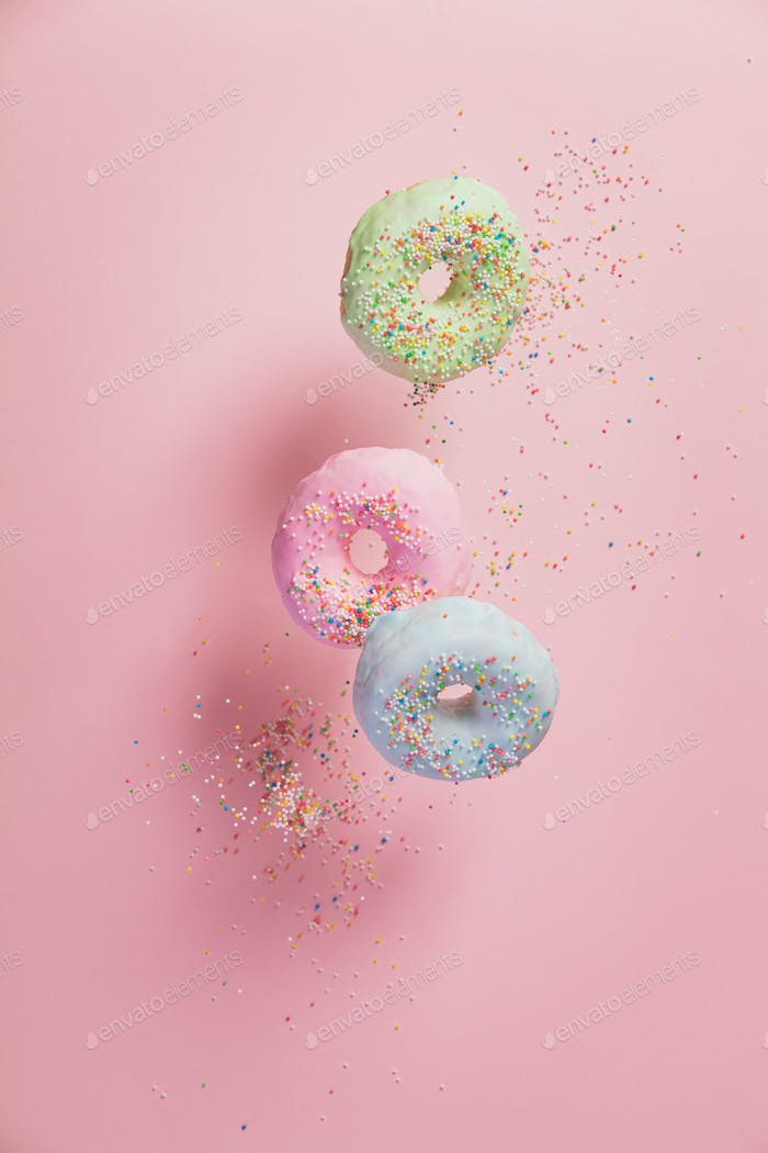 Sweet and colourful doughnuts with sprinkles falling or flying i