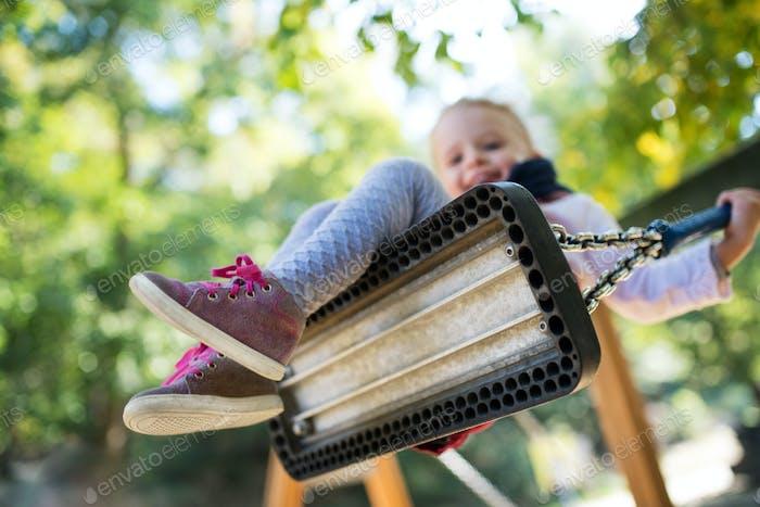 Low-Winkelansicht eines kleinen Kleinkindes Mädchen auf einer Schaukel auf einem Spielplatz