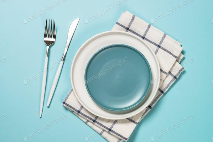 Tischgestell mit weißem Teller und Besteck auf blau