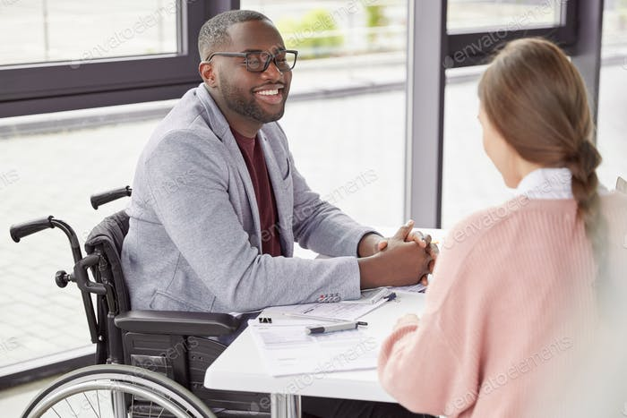 Handsome cheerful black male invalid in wheelchair involved in charity, meets with female investor,