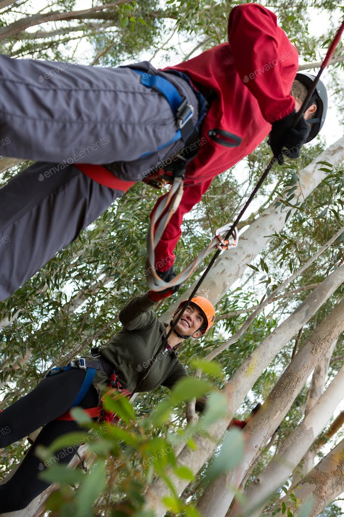 Man helping woman to cross zip line in the forest