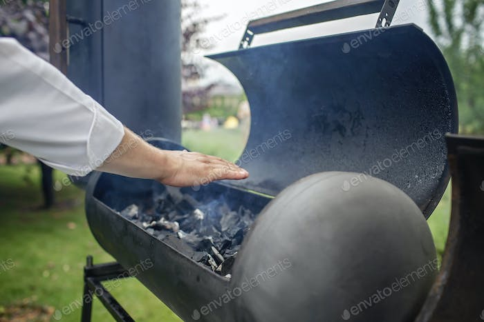 Smoker grill in home backyard, family patio, outdoor bbq party on open air, green garden background