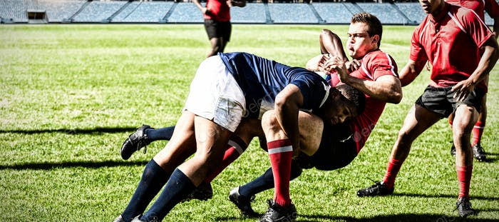 Digital composite image of team of rugby players tackling each other to win the ball in stadium