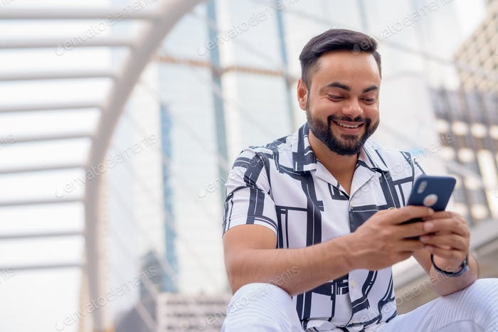Happy young bearded Indian man using phone and sitting in the city outdoors