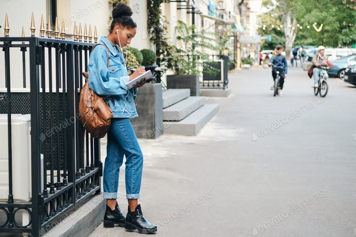 African American student girl in denim jacket with backpack and notepad studying on city street