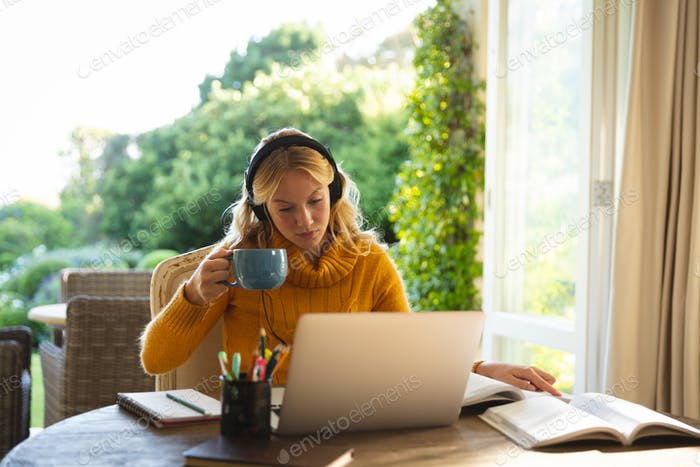 Caucasian woman working in living room at home, wearing headphones and using laptop, holding coffee