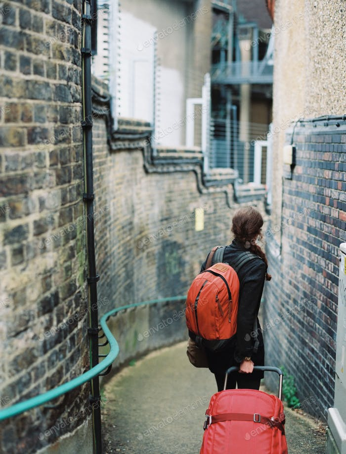 A woman walling down a narrow street, pulling a suitcase and holdin an orange backpack.