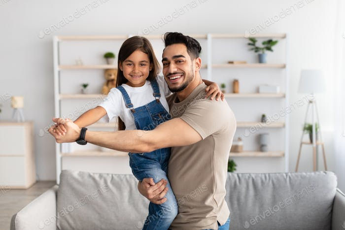 Dad and daughter dancing in living room together