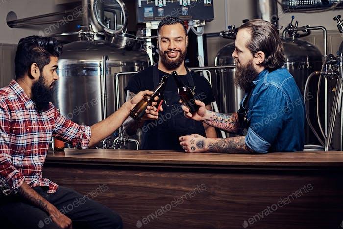 Drei bärtige interrassische Freunde trinken Craft Bier in einer Brauerei.