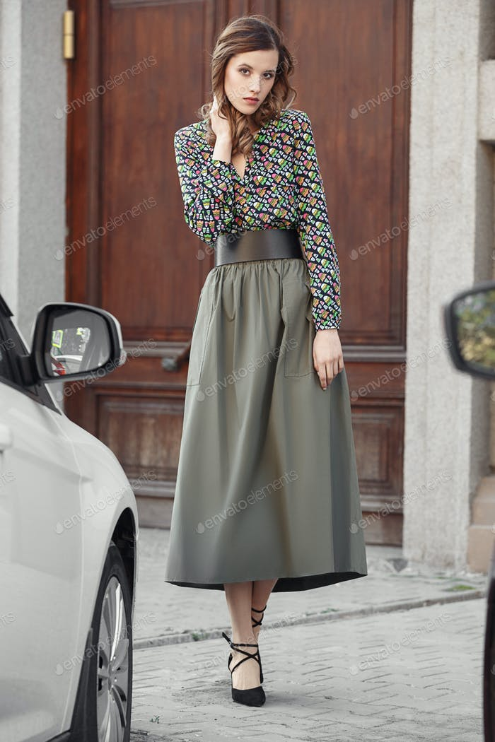 Stylish brunette girl dressed in motley blues and long gray skirt poses in the city street on a