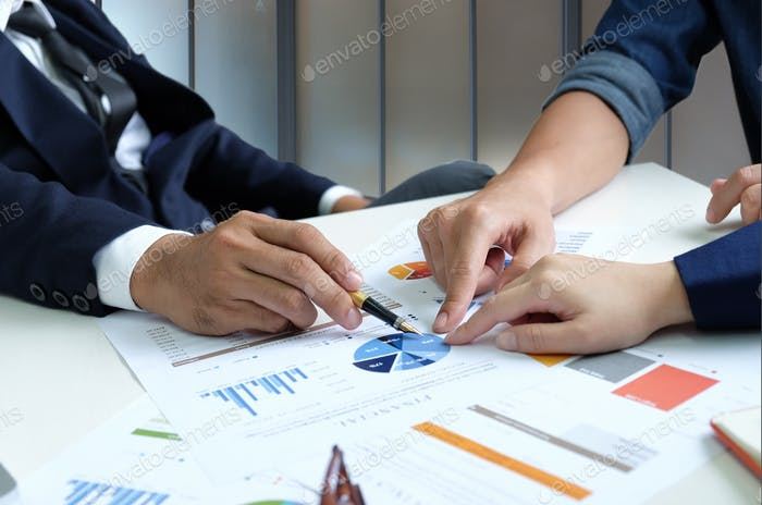 Businessteam are analyzing graphs data.