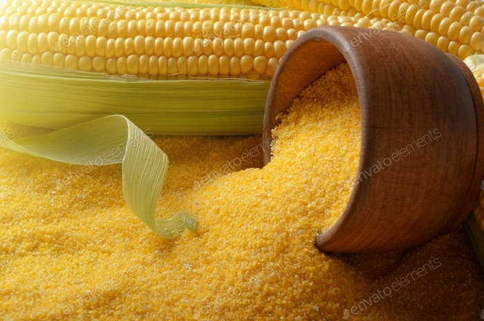 Ripe fresh organic sweet corncob and wooden bowl closeup on grit