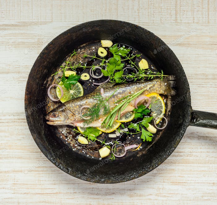 Regenbogenfische in Bratpfanne mit Kräutern und Gewürzen