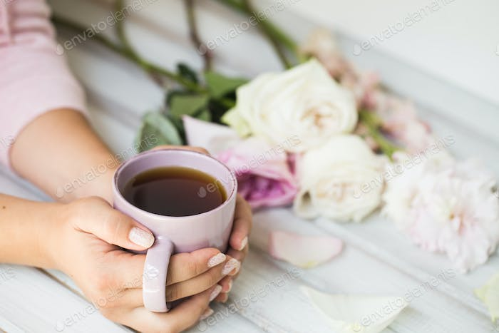 woman holding hot cup of tea on a wooden background. Morning, drink, break