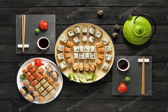 Set von Sushi Maki und Rollen in schwarzem rustikalem Holz.