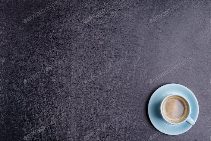 Frisch gebrühtes aromatisches Kaffeegetränk auf einem Hintergrund aus dekorativem schwarzem Kunstleder