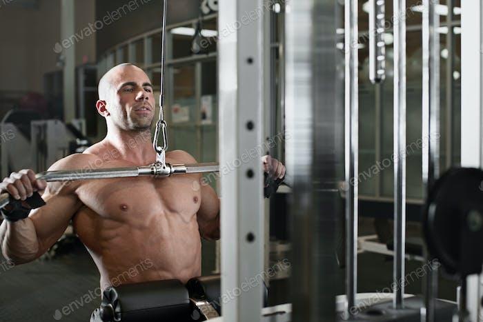 Bodybuilder trainieren im Fitnessstudio während der Verwendung eines Fitnessgeräts