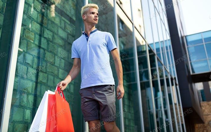 Schöner attraktiver Mann lächelnd Einkaufen in der Stadt
