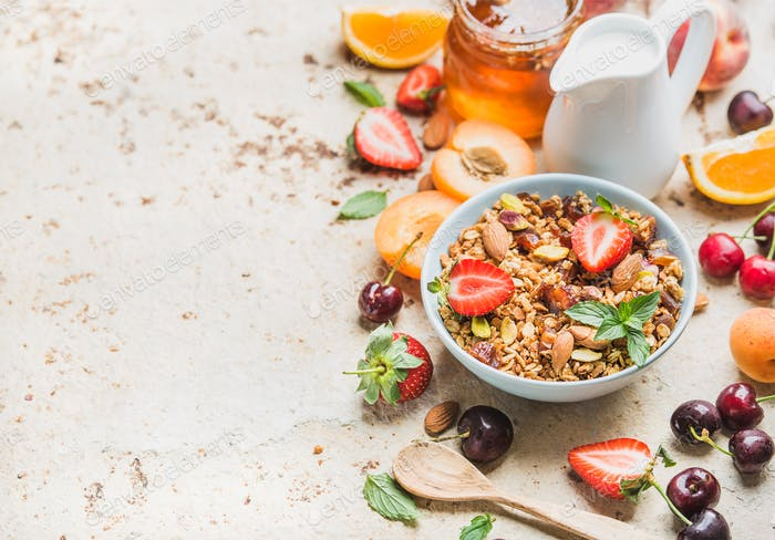Healthy breakfast ingredients. Bowl of oat granola with milk, fresh fruit, berries and honey