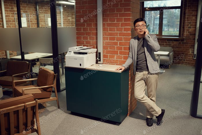 Modern Asian Man Speaking by Smartphone in Office