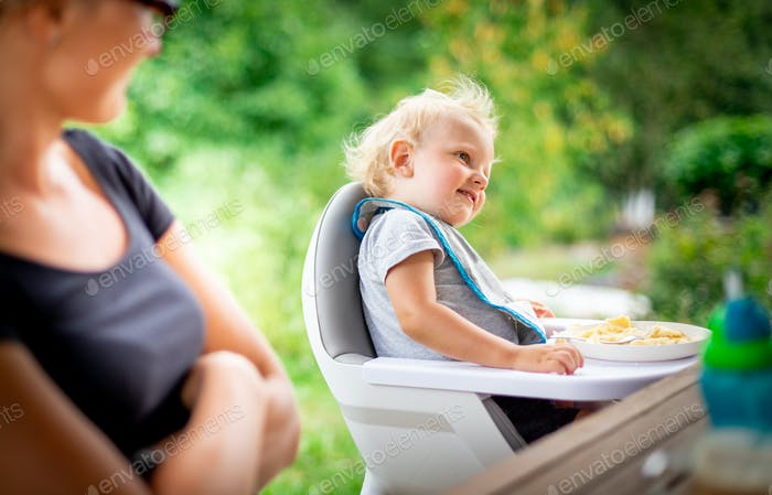 Baby sitting in high chair eating with his mom outdoor