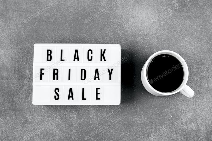 Black friday sale word on lightbox and cup of coffee on red background table. Flat lay, top view