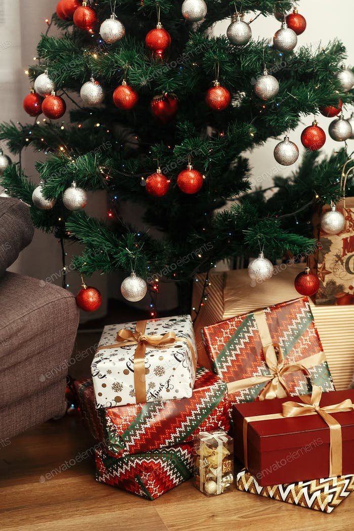 Luxury golden gifts and toys under beautiful christmas tree in room
